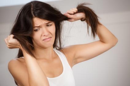 Frau ist unglcklich mit Spliss in den Haaren